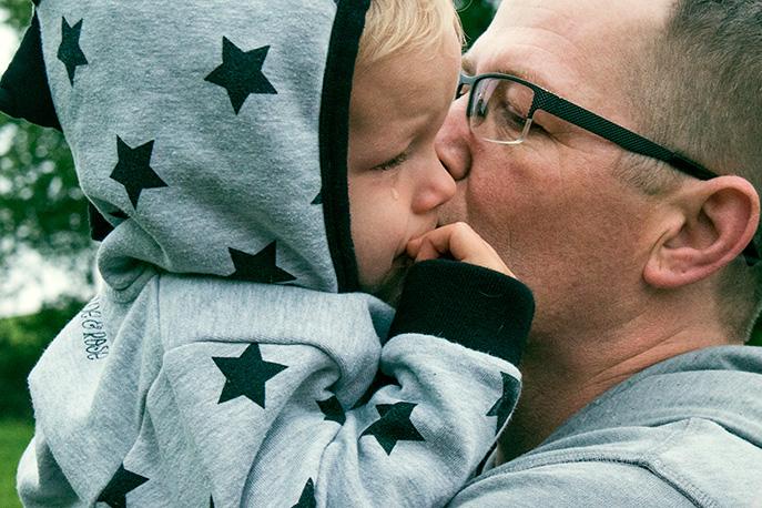 Familienfoto: kleiner Junge weint und ist bei Papa auf dem Arm. Der Papa gibt ihm einen Kuss auf die Wange.