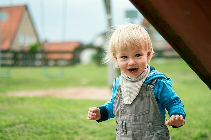 Kinderfotografie Emmerthal/Hameln: Portrait eines Jungen, der unter einer Rutsche steht und lacht