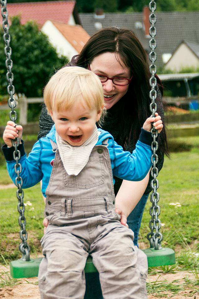 Kinderfotografie Emmerthal/Hameln: Portrait von einem Jungen, der lachend auf der Schaukel sitzt, während er von seiner Mama angeschubst wird