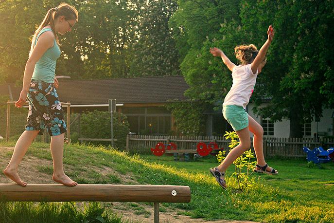 Foto bei Sonnenuntergang auf einem Spielplatz in Hameln. Zwei Kinder spielen auf einem Balancebalken