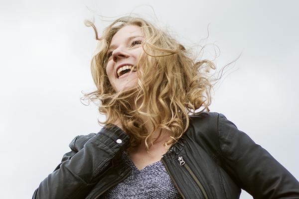 Portrait einer lachenden blonden Frau aus der Froschperspektive, deren Haare im Wind wehen in Groß Berkel bei Hameln