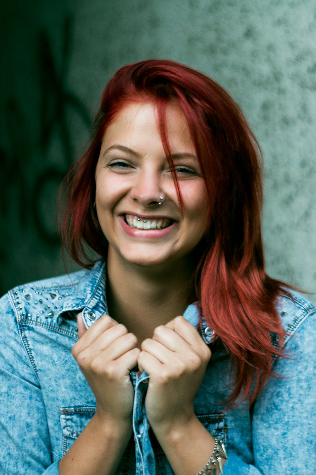 Portrait einer lachenden jungen Frau mit roten Haaren und Piercings aufgenommen in Hameln