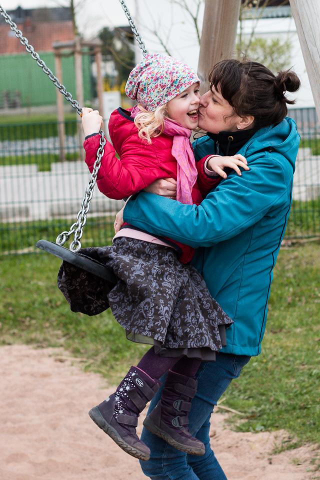 Familienfotografie: eine Mama küsst ihr sich freuendes Kind, das es beim Schaukeln aufgefangen hat