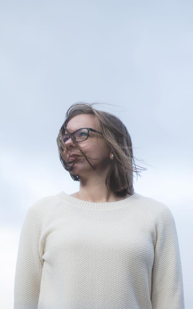 Portrait einer Frau mit Brille und schulterlangen Haaren, von unten fotografiert. Sie schaut in die Ferne, vom Wind wehen ihr die Haare um das Gesicht. Im Hintergrund ist der blaue Himmel zu sehen.
