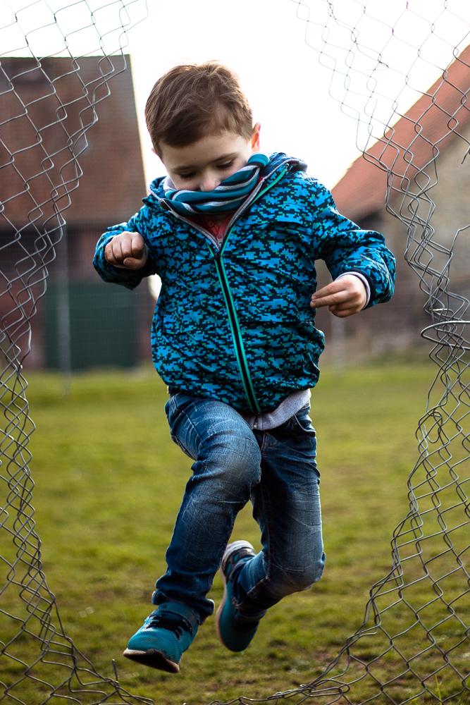Kinderfotografie Emmerthal/Hameln: Portrait eines Jungen, der freudig durch ein Loch im Zaun hüpft