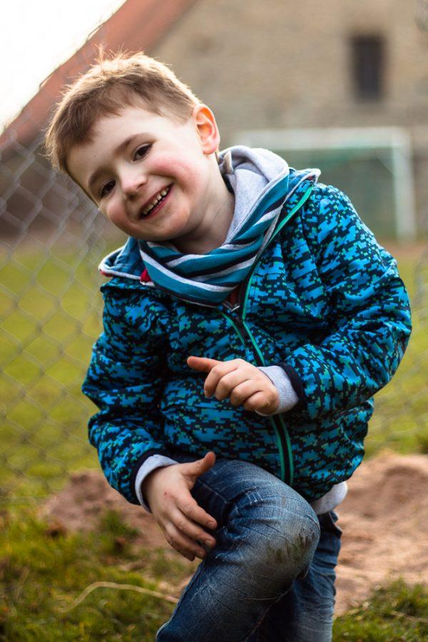 Portrait eines Jungen, der gerade von den Knien wieder aufsteht und dabei in die Kamera lacht.