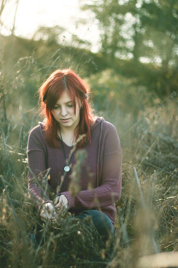 Junge Frau mit roten Haaren in hohem Gras. Sie sitzt und blickt nach unten.