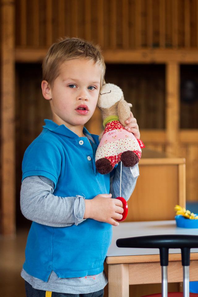 Portrait eines Jungen aus einer Kindergartenreportage/Kindergartenfotografie in Grupenhagen bei Hameln. Er hört sich gespannt eine Spieluhr an.