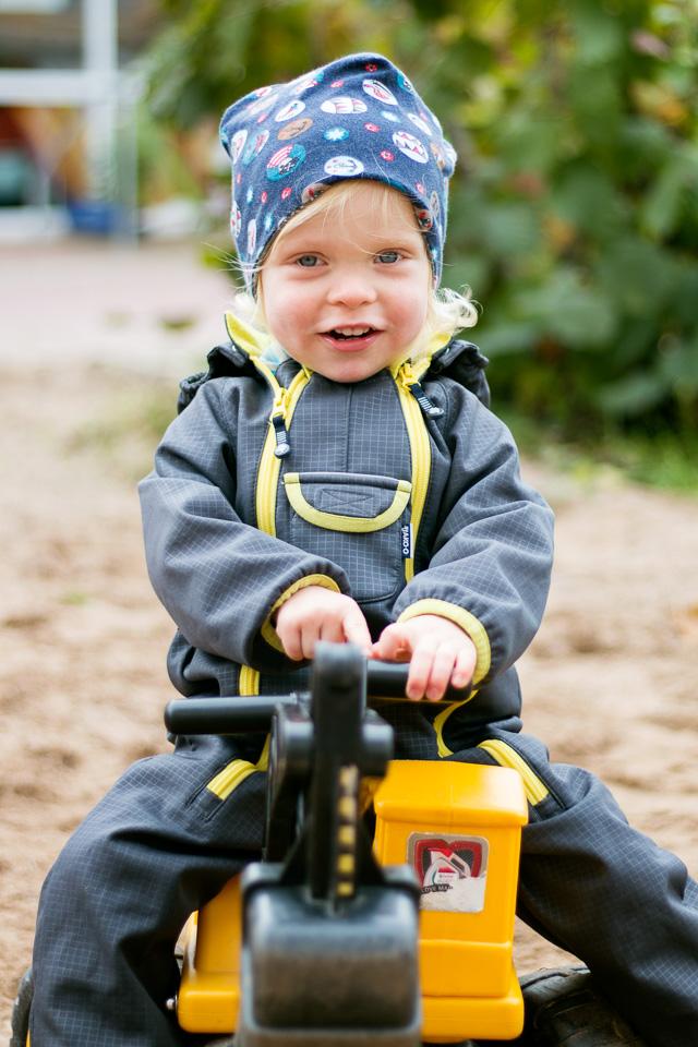 Portrait eines Jungen, der auf einem Bagger sitzt, aus einer Kindergartenreportage/Kindergartenfotografie in Grupenhagen bei Hameln