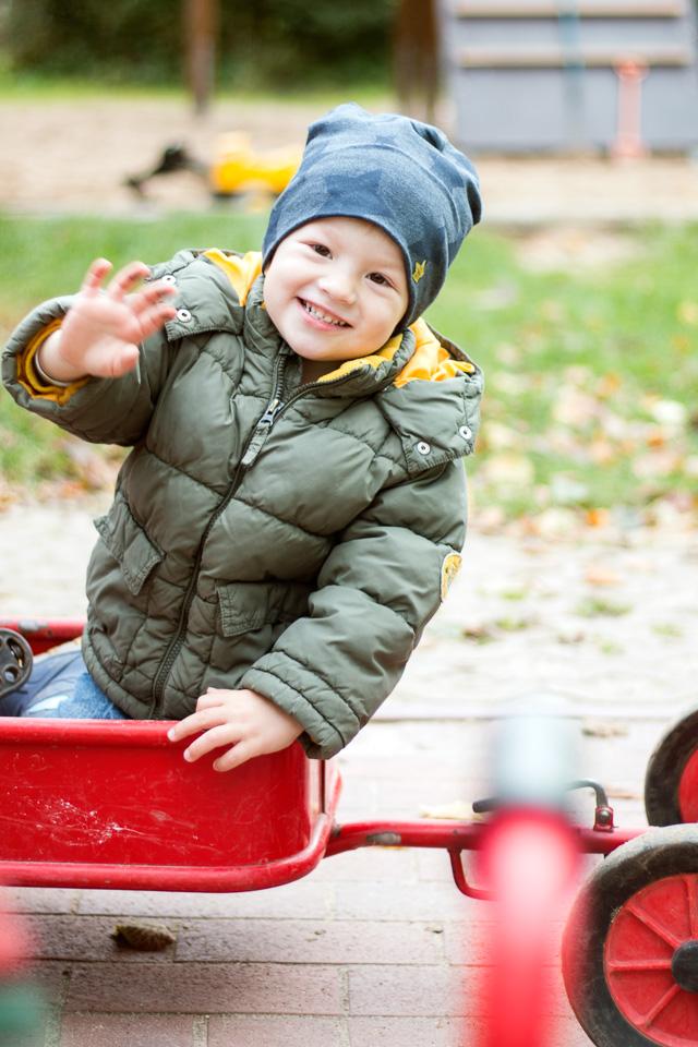 Portrait eines Jungen aus einer Kindergartenreportage/Kindergartenfotografie in Grupenhagen bei Hameln. Er winkt in die Kamera und lächelt.