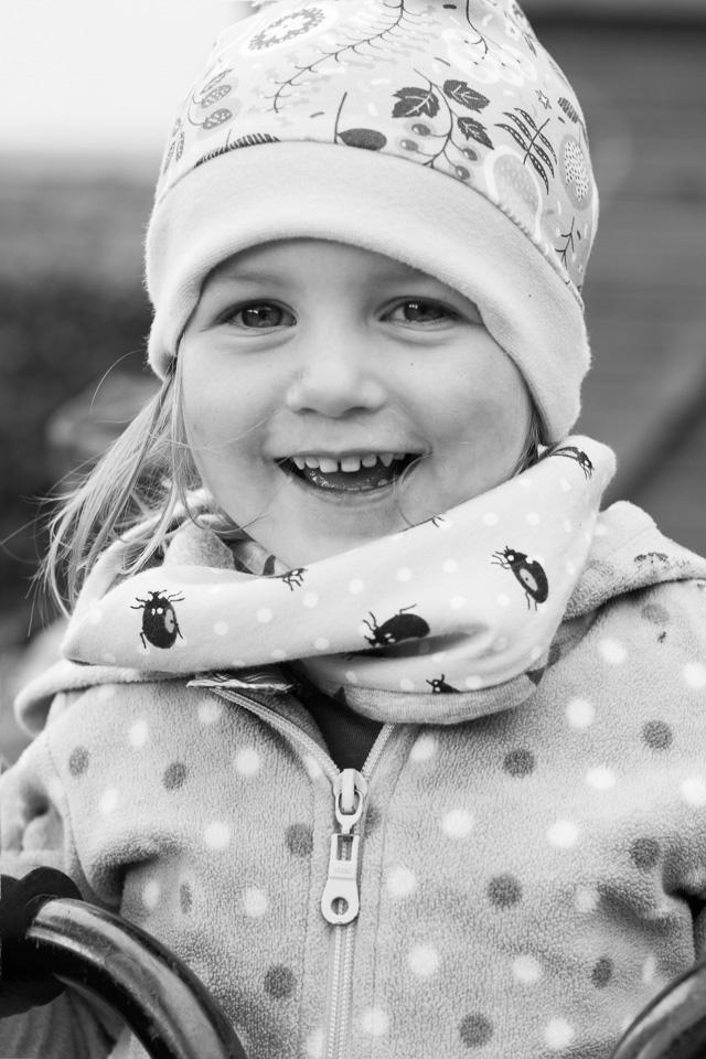 Portrait (schwarz-weiß) eines lachenden Mädchens aus einer Kindergartenreportage/Kindergartenfotografie in Grupenhagen bei Hameln