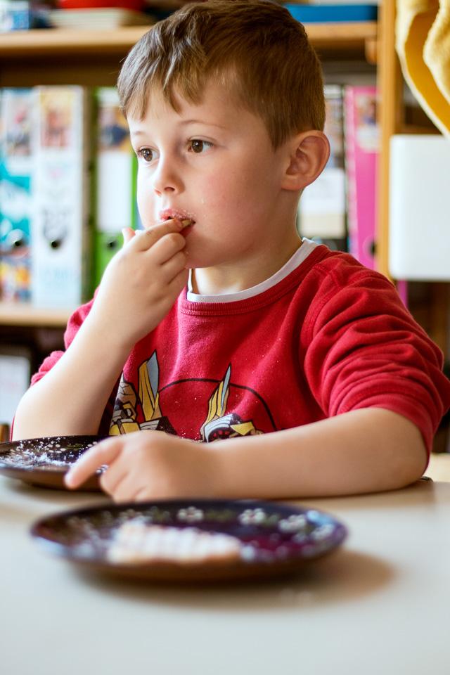 Portrait eines Jungen aus einer Kindergartenreportage/Kindergartenfotografie in Grupenhagen bei Hameln. Er isst am Tisch eine Waffel.