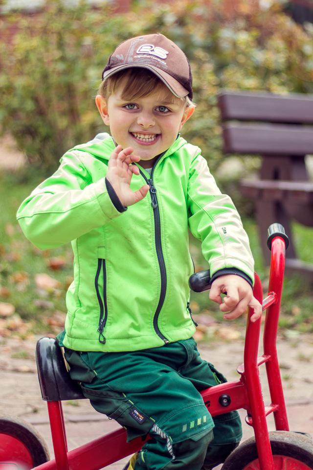 Portrait eines Jungen aus einer Kindergartenreportage/Kindergartenfotografie in Grupenhagen bei Hameln. Er winkt in die Kamera und grinst.