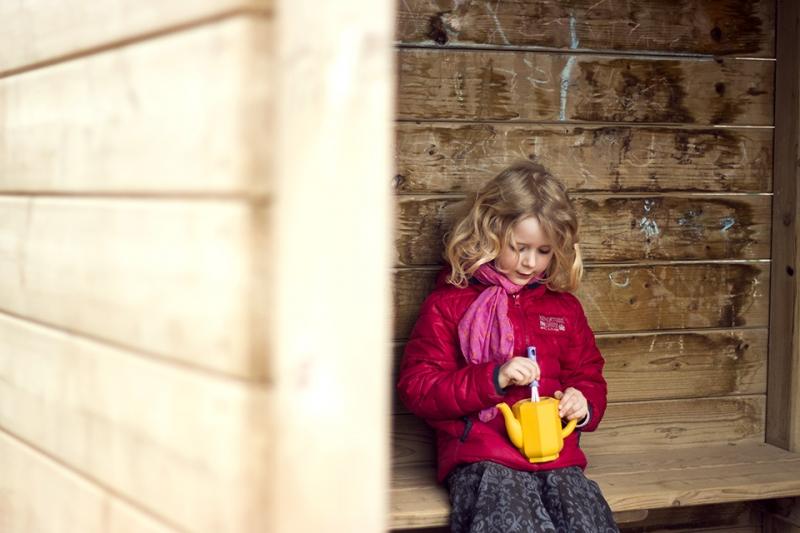 Kinderfotografie: Portrait von einem Mädchen, das auf der Bank einer Spielplatzburg sitzt und kochen spielt